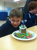 One Todd Schooler poses next to his gingerbread house.